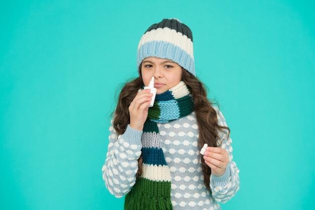 Adem vrij. beste neusspray voor kinderen. meisje houdt neusdruppels vast. allergie. thuisbehandeling. neusdruppels plastic fles. griep concept. symptomen van verkoudheid. bijwerkingen. apotheek industrie. voel beter.