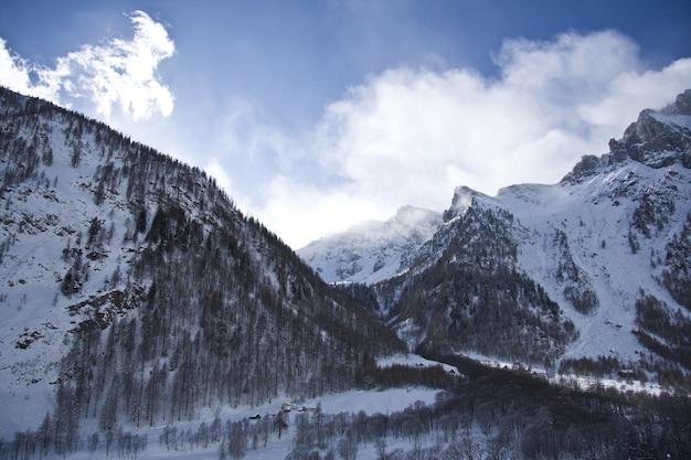 Adembenemend landschap van de met sneeuw bedekte bergen onder een schilderachtige bewolkte hemel