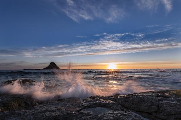 Adembenemend landschap van het water dat naar de kust spettert tijdens de prachtige zonsopgang