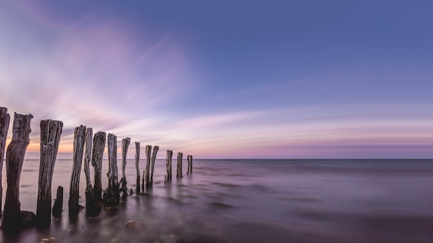Adembenemend landschap van houten stokken in het midden van de oceaan onder de kleurrijke lucht Gratis Foto