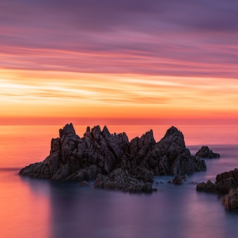 Adembenemend landschap van zeestapels tijdens zonsondergang onder de kleurrijke lucht in guernsey
