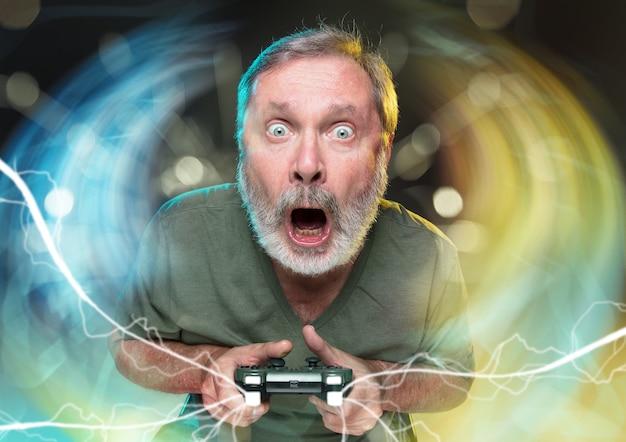 Adembenemend nieuw leven senior man met een videogamecontroller geïsoleerd op een kleurrijke achtergrond