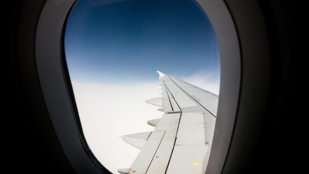 Adembenemend uitzicht op de blauwe lucht vanuit het raam van een vliegtuig