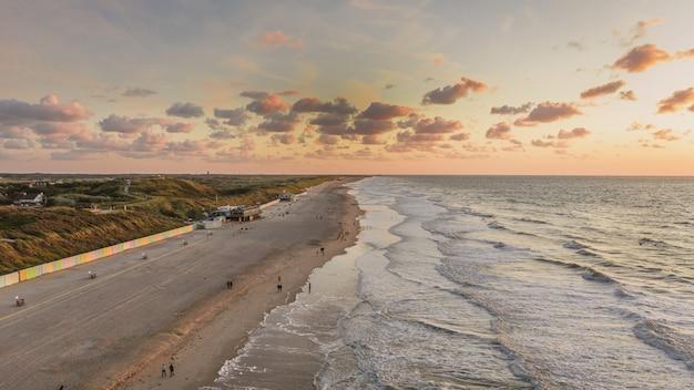 Adembenemend uitzicht op de golvende oceaan onder de bewolkte hemel in domburg, nederland