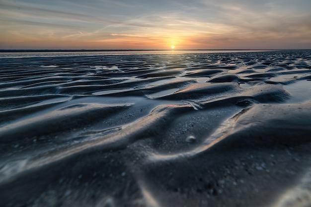 Adembenemend uitzicht op een prachtig strand op een prachtige zonsondergang op de achtergrond