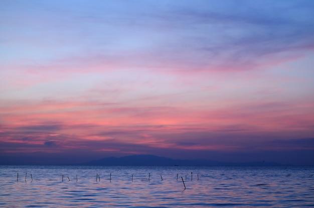 Adembenemende blauwe en paarse kleur van de wolkenlaag op zonsopganghemel over de golf van thailand