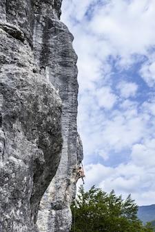 Adembenemende foto van een jonge man die op de hoge rots in champfromier, frankrijk klimt