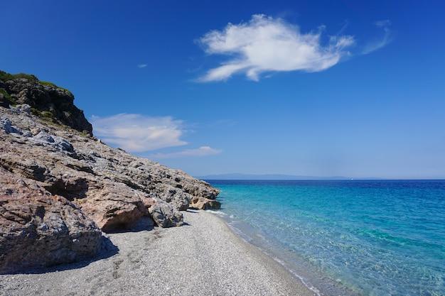 Adembenemende opname van een blauwe zee die samenkomt met een zonnig rotsachtig strand onder de blauwe lucht