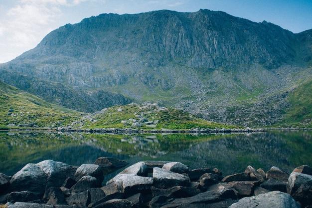 Adembenemende opname van een kristalhelder meer omgeven door rotsen en hoge rotsachtige bergen