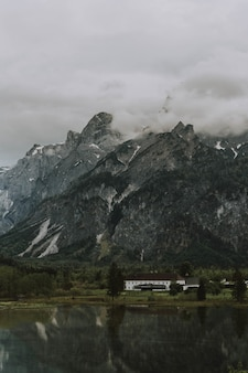 Adembenemende opname van het bruine en witte huis bij het meer en de bergen onder een bewolkte hemel