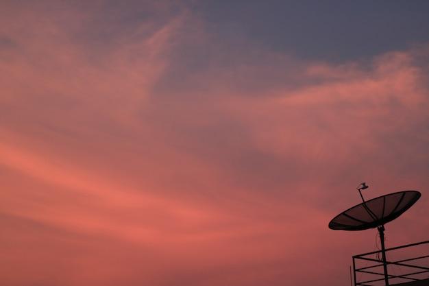 Adembenemende roze en blauwe zonsondergang afterglow met het silhouet van satellietschotel