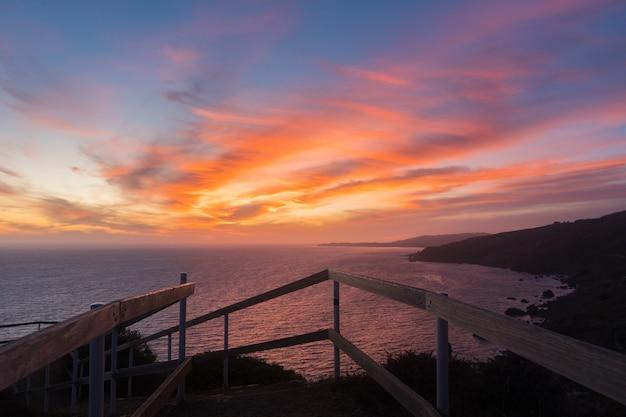Adembenemende zonsondergang over de kalme oceaan omgeven door heuvels