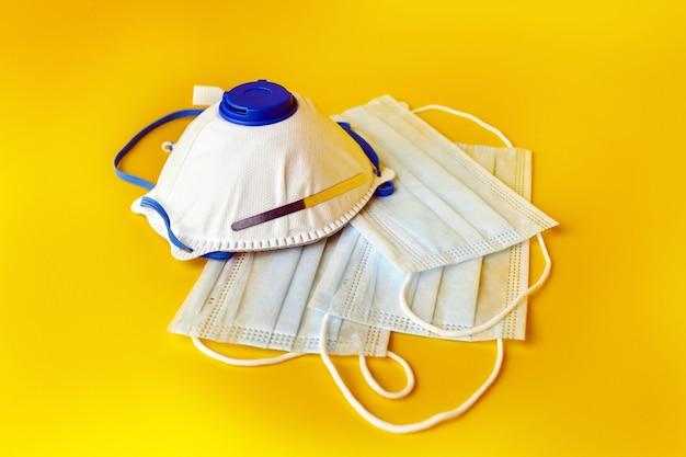Ademhalingsapparaat en chirurgische gezichtsmaskers op geel oppervlak