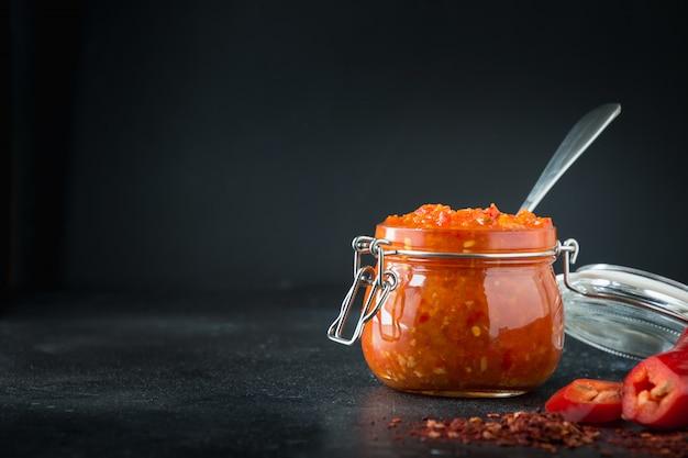 Adjika hot chili peper saus plakken harissa in glazen pot. tunesië, georgische en arabische keuken. horizontaal.