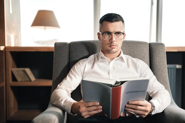 Administratief recht. slimme veelbelovende advocaat die de administratieve wet leest die zich voorbereidt op een belangrijk examen