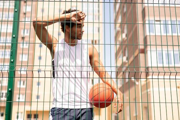 Adolescente basketbalspeler in sportkleding die tegen het hek van de baan leunt terwijl hij rust na de training