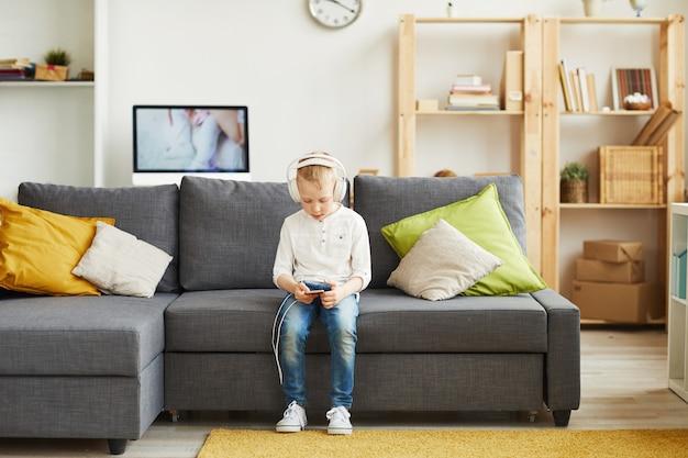 Adolescente jongen die muziek op smartphone kiest