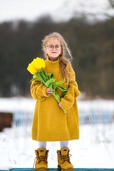 Adorabe meisje droeg volwassen oversized trui en grote vaders laarzen. mooi jong meisje in glazen die zich op bank met boeket van gele tulpen in sneeuw de winterdag bevinden.
