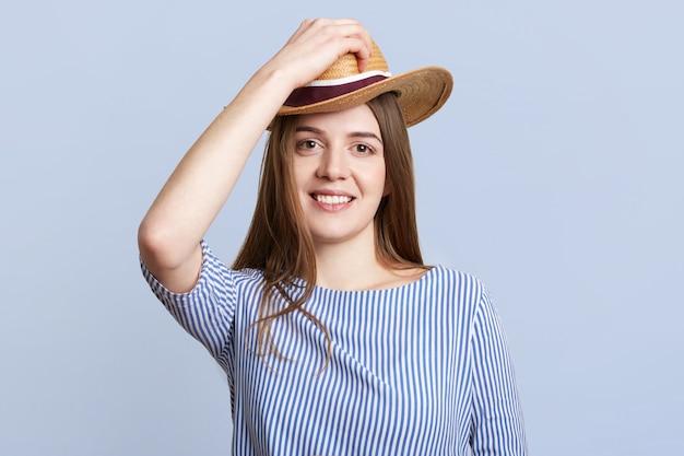 Adorbble vrouw in gestreepte blouse draagt strooien hoed op het hoofd, in een goed humeur, zoals verheugt zich over nieuwe aankopen, geïsoleerd op blauw. tevreden vrouw met vrolijke expressie binnen.
