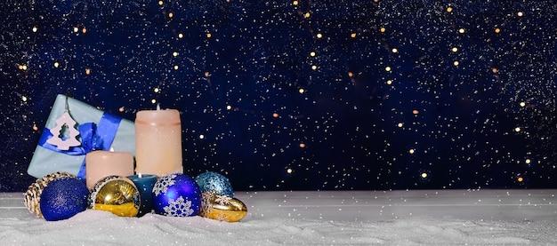 Advent-kerstsamenstelling van balkaarsen met heldere bokeh en sneeuw