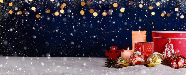 Adventkerstmis of nieuwjaarssamenstelling van balkaarsen en ornamenten met heldere bokeh en sneeuw