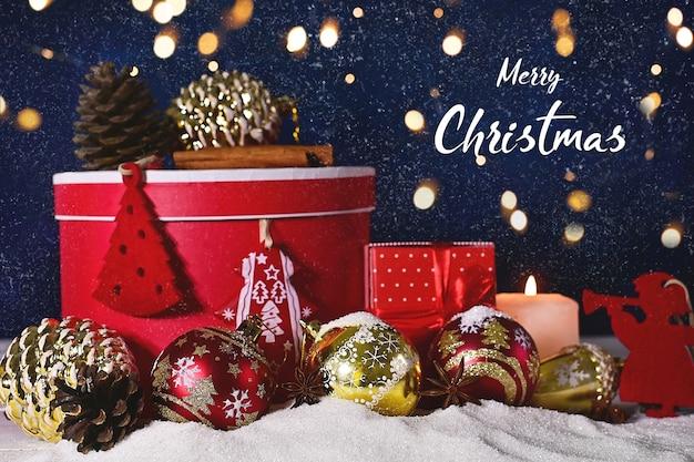 Adventkerstmis of nieuwjaarssamenstelling van ballenkaarsen en ornamenten met heldere bokeh en sneeuw