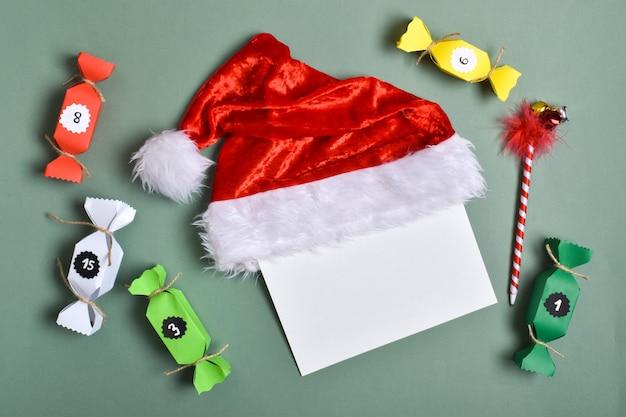 Adventskalenders van gekleurd papier in de vorm van snoepjes. blanco papier voor het schrijven van taken voor de adventskalender. ruimte kopiëren. plat lag, bovenaanzicht.