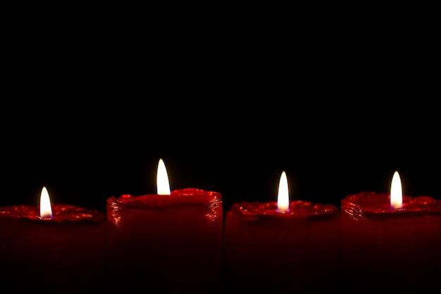 Adventsset van vier rode kerstkaarsen met rustig brandende vlammetjes.