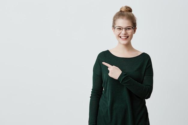 Advertentie concept. jonge dame met blond haar, stijlvolle bril in groene trui en vrolijke uitdrukking die wat informatie of promotie demonstreert, wijzend met de vinger op de kopie ruimte