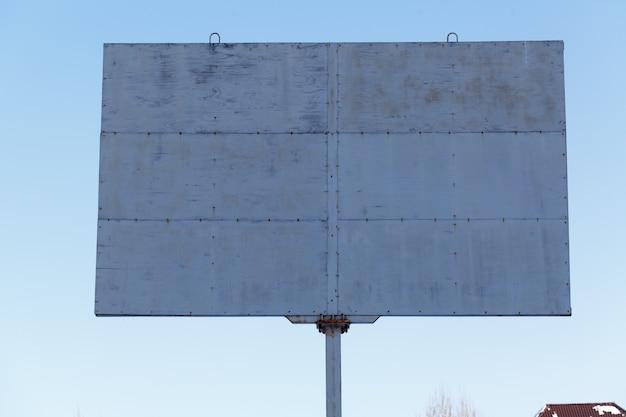 Adverterend aanplakbord op blauwe hemel in stedelijk