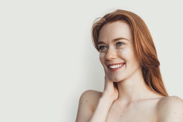 Adverterende kaukasische gembervrouw met sproeten en naakte schouders die op een witte studiomuur met vrije ruimte glimlachen