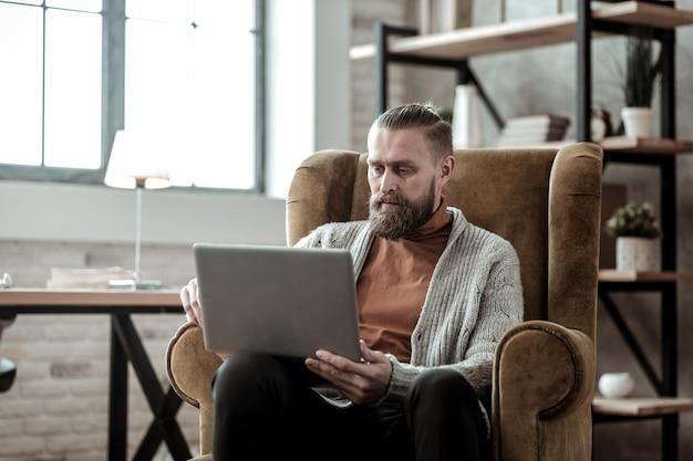 Adviseur aan het werk. donkerharige privé-adviseur die zijn laptop gebruikt terwijl hij in een leunstoel zit en aan het werk is