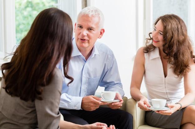 Adviseur die beleggings- en pensioenadvies geeft aan senior vrouw en man