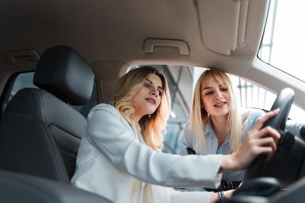 Adviseur die het interieur van de auto aan een klant toont