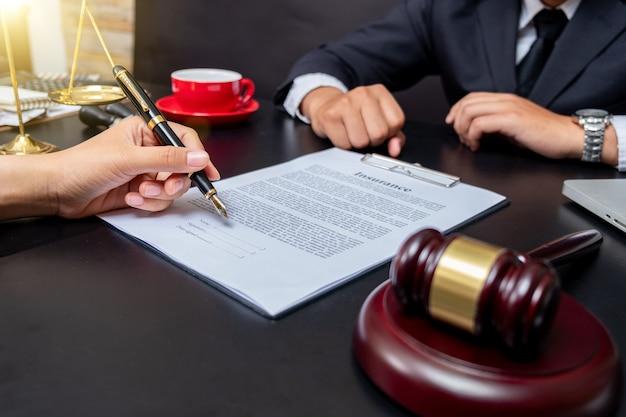 Advocaat detail van een rechter die aan zijn bureau zit, nieuwe wetten en wetgeving bestudeert en aantekeningen maakt. selectieve aandacht.