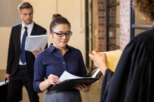 Advocaat die documenten bekijkt en met onderneemster in bureau interactie aangaat