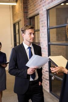 Advocaat die documenten bekijkt en met zakenman in bureau interactie aangaat