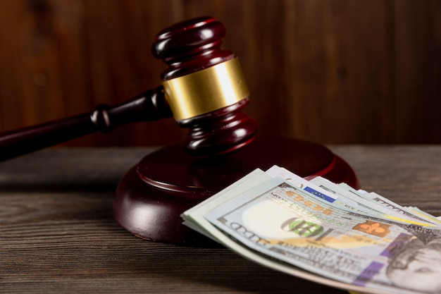 Advocaat en advocaat concept. houten rechter hamer en dollars op tafel.