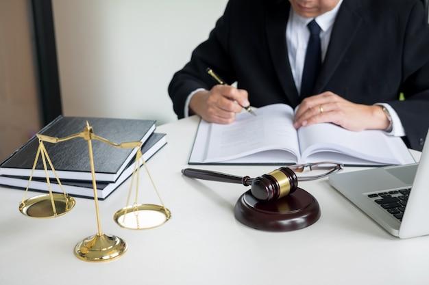 Advocaat hand schrijft het document in de rechtbank (gerechtigheid, wet) met klinkende blok en gouden gewicht