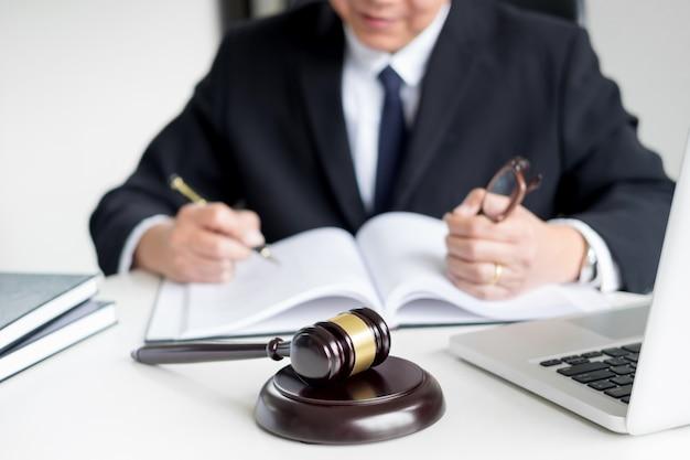 Advocaat hand schrijft het document in de rechtbank (gerechtigheid, wet) met klinkende blok
