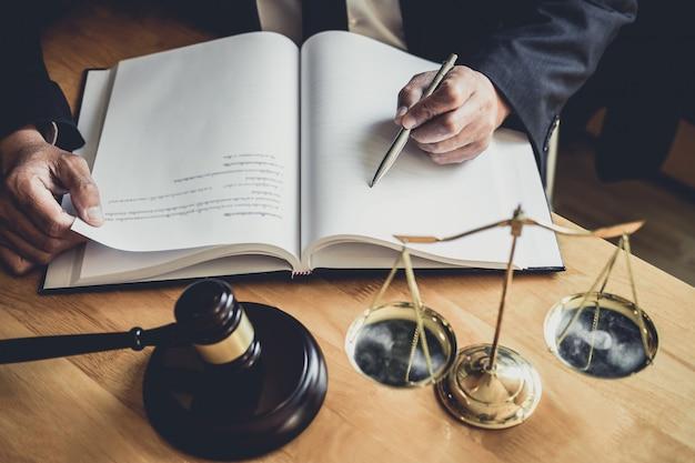 Advocaat of rechter die werkt met contractpapieren, documenten en hamer en schalen van justitie