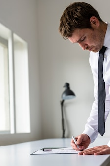 Advocaat of uitvoerende macht die een contract ondertekent, dat op wit bureau wordt geplaatst.