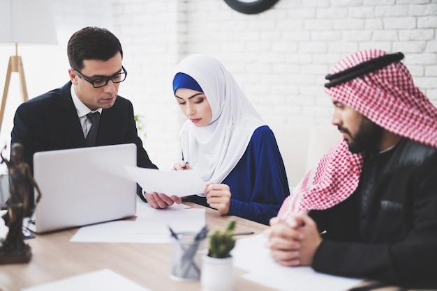 Advocaat op kantoor met arabische man en vrouw.