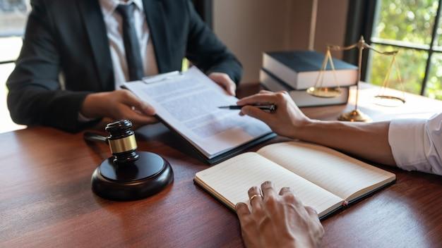 Advocaat samen met cliënt bespreken over wettelijke wetgeving in rechtszaal