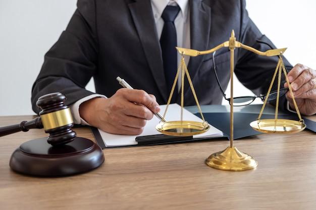 Advocaat werkt aan een document en verslag van de belangrijke zaak en houten hamer