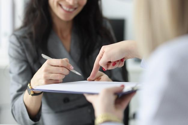 Advocaat wijst naar verzekeringscontract en laat de klant aan de vrouw zien waar hij een aankoop moet ondertekenen