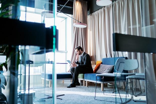 Advocaat zittend in zijn kantoor op de bank met hand op de kin en tablet gebruiken voor werk.