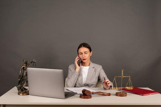 Advocaten kantoor. standbeeld van justitie met schalen en advocaat die op een laptop werkt. juridisch recht, advies en rechtvaardigheidsconcept