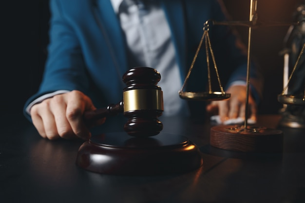 Advocaten kantoor. standbeeld van justitie met weegschaal en advocaat die aan laptop werkt. juridisch recht, advies en rechtvaardigheidsconcept.