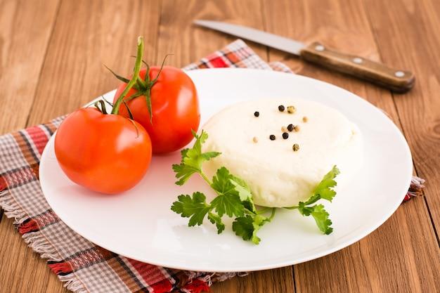 Adyghe-kaas, tomaat en peterselie op een plaat op een houten tafel